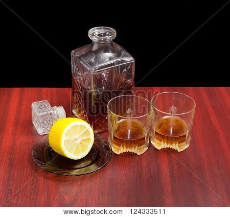 Decanter and two glasses with whiskey stopper from the decanter and lemon on a saucer on a wooden table on a dark background