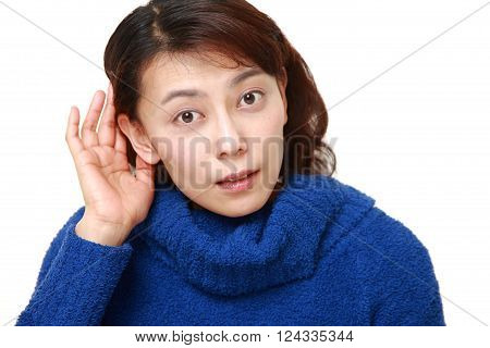 woman with hand behind ear listening closely