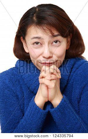 Asian woman folding her hands in prayer