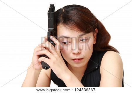 portrait of Asian woman with a handgun thinks