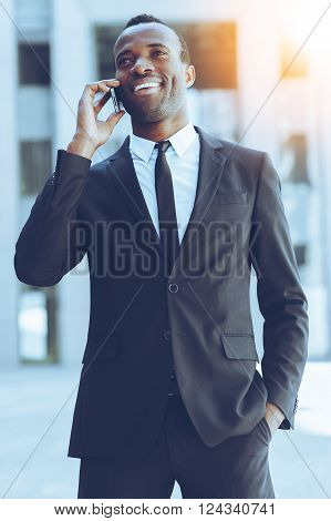 Good business talk. Happy young African man in formalwear talking on the mobile phone and smiling while standing outdoors