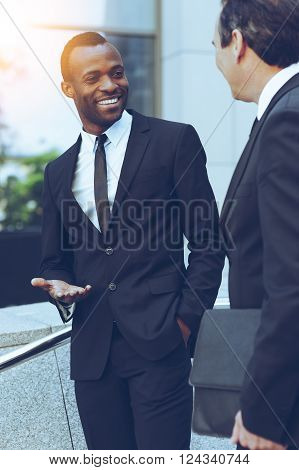 Talking about business. Two cheerful business men talking and gesturing while standing outdoors ** Note: Visible grain at 100%, best at smaller sizes