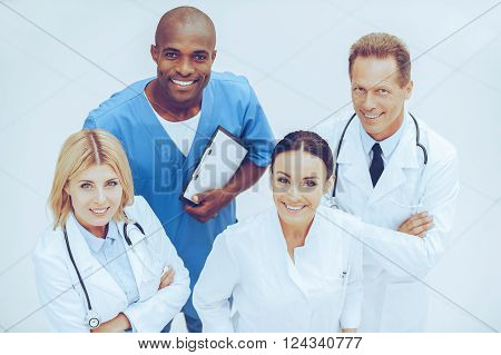 Taking care of your health.. Top view of four confident doctors standing close to each other and smiling