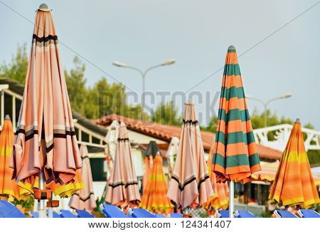 Many closed orange parasols on the beach at the end of a hot summer day