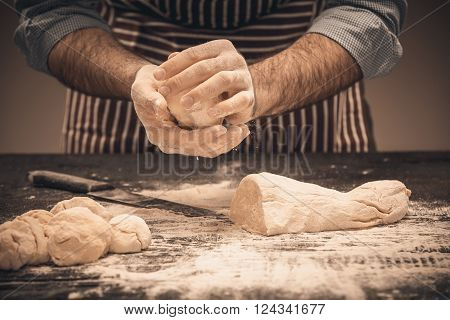 Male hands knead the dough. Chef cooking bread and bun