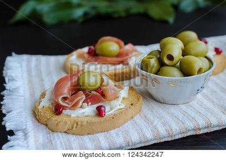 Spanish food tapas. Toasted bread with serrano ham and olives. Sandwiches with prosciutto. Selective focus.