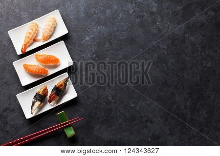 Sushi set and chopsticks on stone table. Top view with copy space