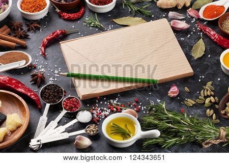 Notepad for your recipe with herbs and spices over black stone background