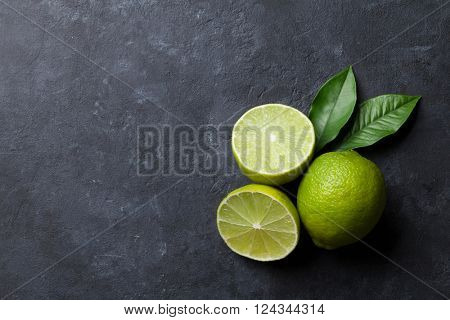 Fresh limes on stone background. Top view with copy space