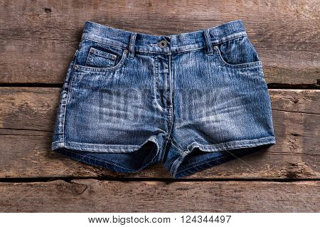 Denim shorts on aged shelf. Female shorts on retro showcase. Vintage denim shorts on shelf. Lady's shorts in classic style.