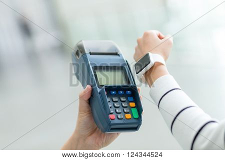 Woman using smart watch to pay by NFC technology