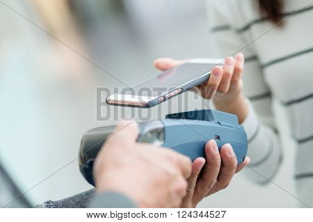 Woman using mobile phone for paying