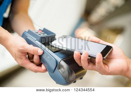Customer using cellphone for pay by NFC technology