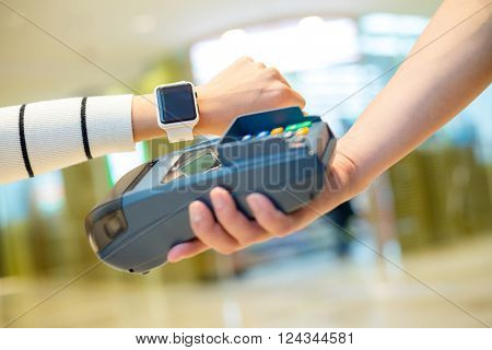 Woman pay on pos machines with smart watch