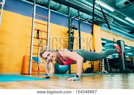 Fitness girl training trx workout in gym. Fitness coach show trx workout in gym. Athletic girl working on trx in gym