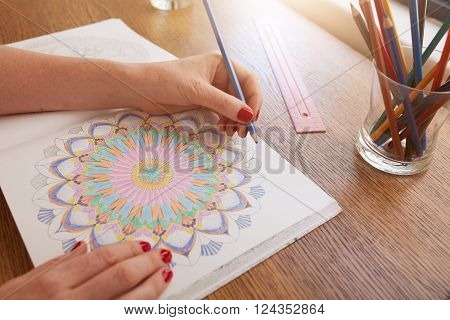 Close up image of woman hands drawing in adult colouring book on a table at home.