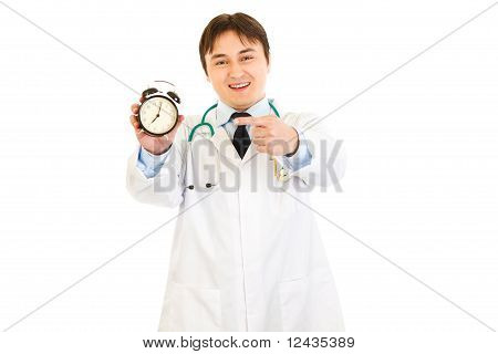 Smiling medical doctor pointing finger on alarm clock isolated on white