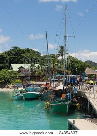 La Digue - November 10 2014: Boats and yachts stand at the port of the island of La Digue and people unload cargo at the port on a sunny day November 10 2014 the island of La Digue Seychelles