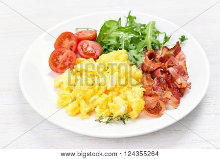 Scrambled eggs bacon and vegetable salad close up view
