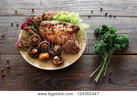 Homemade supper with fresh vegetables. Grilled pork meat with lettuce and mushrooms. Homemade steak on wooden table.