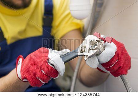 plumber screwing plumbing fittings in bathroom. focus on valve