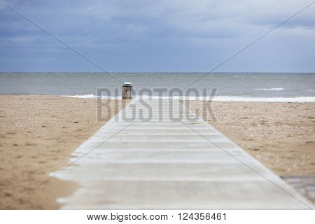 concrete path on deserted north sea beach with garbage can and cloudy sky