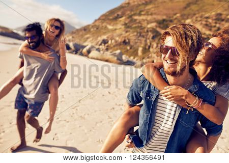 Young men piggybacking women on the sea shore. Mixed race young people enjoying summer vacation at beach.