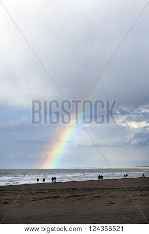 people stroll on north sea beach in holland near scheveningen with cloudy sky and rainbow