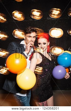 Hipster friends clubbing dancing celebrate concept on dance club background. Woman with  colorful balloon and happy man dance on lights background. Concept of night lifestyle.