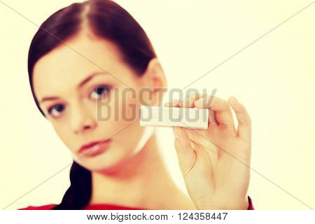 Unhappy young woman holding pregnancy test