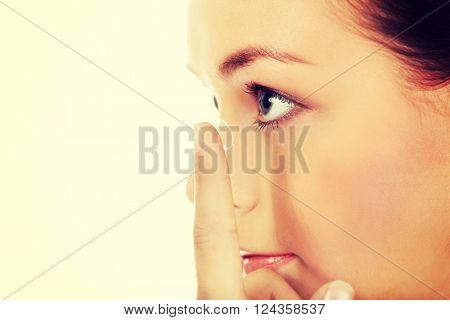 Beautiful young woman putting a contact lens
