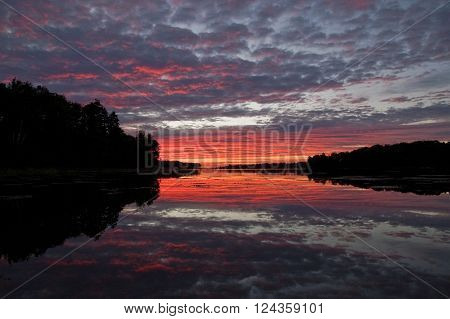 Sunrise reflected in the water of a bay along Maine's coast