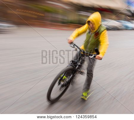 Cyclist in traffic on the city roadway. Intentional motion blur