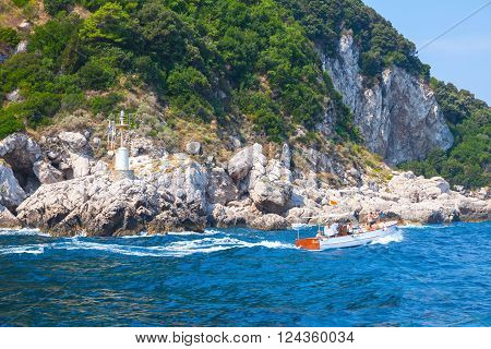 Motorboat With Tourists Goes Near Coastal Rocks
