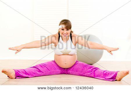 lächelnd schön schwanger Woman doing stretching-Übungen
