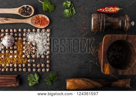 Composition of chick-peas and spice with wooden tableware on the dark table