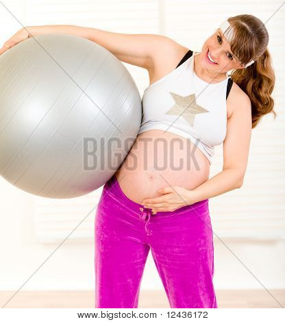 Smiling beautiful pregnant woman holding fitness ball and touching her belly at living room