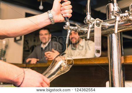 Bartender pouring beer from tap, selective focus