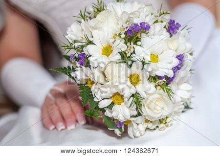 Bride holding white roses and chrysanthemums bouquet in hands