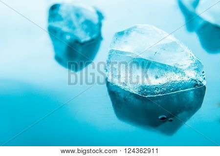 Piece of ice on the blue background