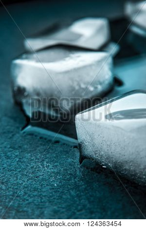 Ice cubes on the dark stone table vertical