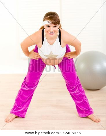 Smiling beautiful pregnant female making gymnastics at home