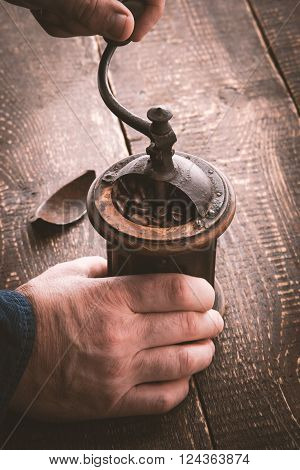 Old coffee mill in the hands vertical