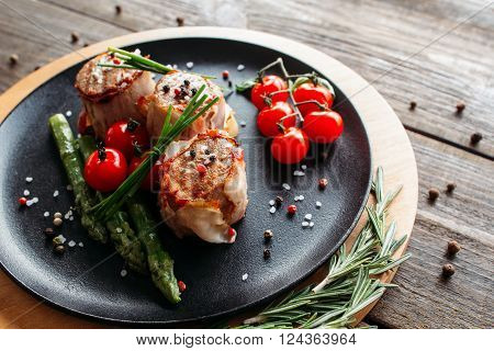 Grilled pork dish with fresh vegetable spices. Food photography of grilled pork medallions with herbs and spices. Tasty cook meat with  vegetables on dark wooden background.