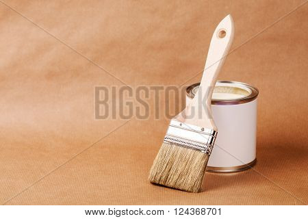 Paint can with brush, lacquer or varnishing wooden floor.