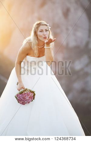 Smiling bride holding big wedding bouquet