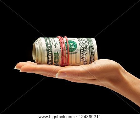 Hand is giving bundle of one hundred US dollars banknotes isolated on black background. Business concept