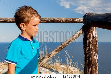 Portrait of pensive serious cute boy on background of mountains Italy