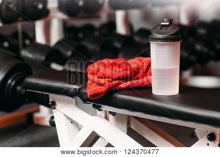 Sport, fitness, healthy lifestyle and bodybuilding concept - close up of bottle with water and wet towel in gym background.  Set of personal sport stuff lay on training  bench in fitness gym