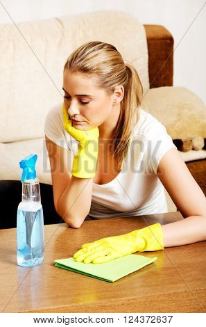 Tired young woman cleaning table in yellow gloves